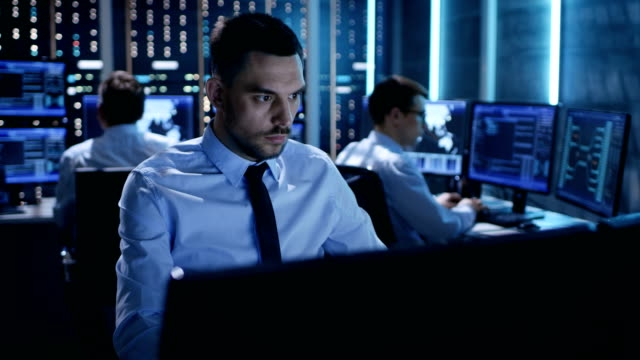 Close-up of Operations Engineer Working on His Computer With Multiple Displays in Monitoring Room. In the Background His Colleagues with Graphics and Various Data on Their Monitors. video