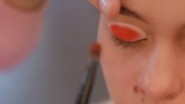 オレンジ色のまぶたを塗るクローズアップ - まぶた点の映像素材/bロール