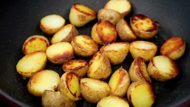 closeup of pan fried potatoes being seasoned with salt and pepper. slow motion. - smażony ziemniak filmów i materiałów b-roll