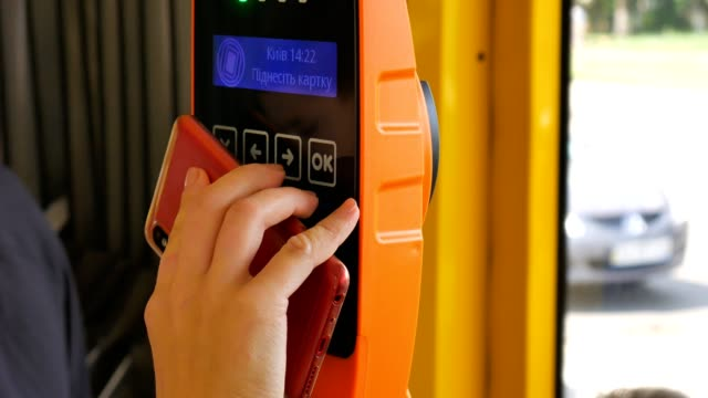 vídeos de stock e filmes b-roll de closeup of paying by a telephone using paypass reader on a ticket vending machine with terminal. ukraina kiev. - paying with card contactless