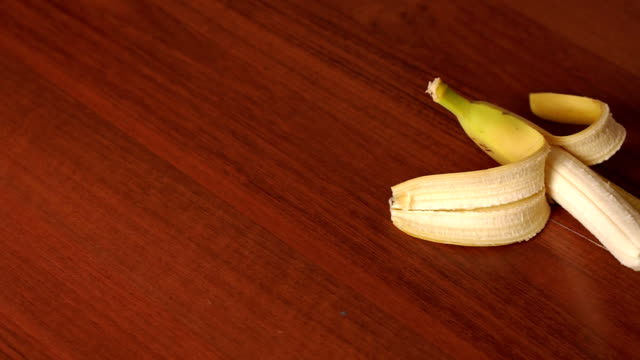 Close-up of peeled banana on wooden background. video