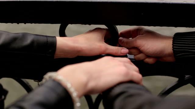 Close-up of pendant lovers hang a lock on bridge. video