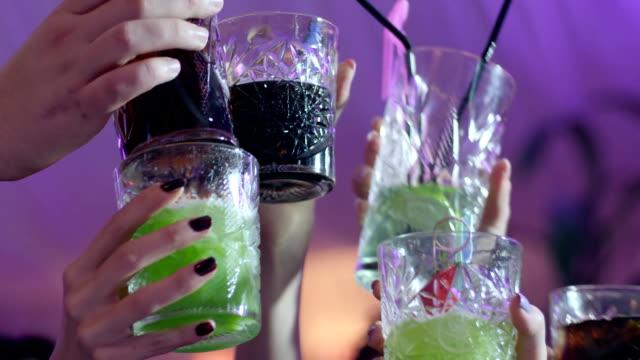 nahaufnahme der menschen hände machen toast mit brille mit bunten alkoholische cocktails im club - anstoßen stock-videos und b-roll-filmmaterial