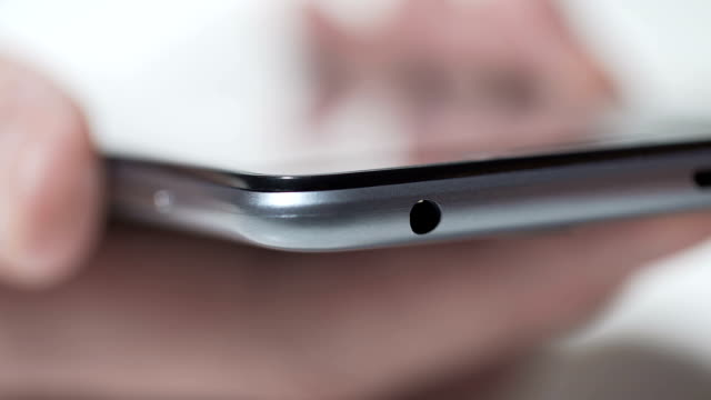 Closeup of person connecting headphones to modern smartphone, service center video