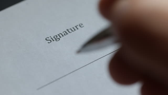 closeup of person signing document - firma video stock e b–roll