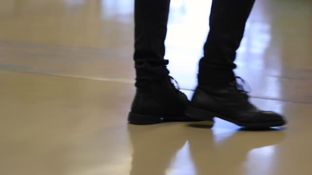 すべての黒のジーンズとスローモーションで歩くブーツを身に着けている人のクローズ アップ - 革点の映像素材/bロール