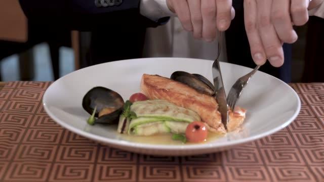 Closeup da placa com frutos do mar e prato de legumes no restaurante requintado. Homem de terno está a comer o prato. - vídeo