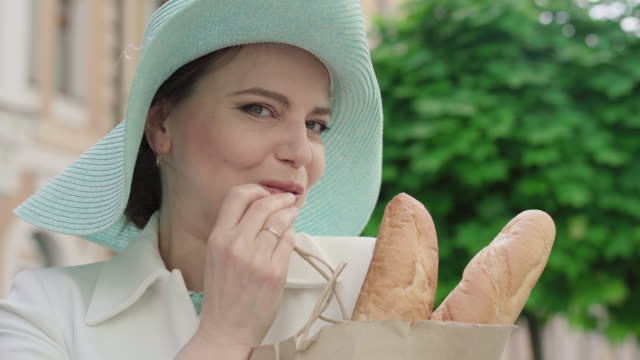 Close-up of positive elegant woman smelling tasty baguette and eating piece of bakery. Portrait of confident beautiful Caucasian lady posing on city street on summer day. Tourism concept. Close-up of positive elegant woman smelling tasty baguette and eating piece of bakery. Portrait of confident beautiful Caucasian lady posing on city street on summer day. Tourism concept. one mid adult woman only stock videos & royalty-free footage
