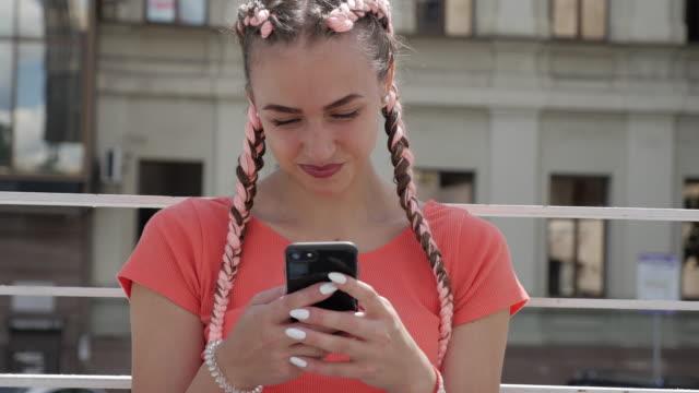 vídeos y material grabado en eventos de stock de primer plano de mujer positivo envío de mensajes en el teléfono mientras se relaja al aire libre - moda playera