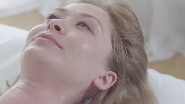 närbild av positiv ung kvinna med nålar i ansiktet öppna ögon och leende på kameran. porträtt av blond gråögd tjej njuter akupunktur. alternativ kinesisk medicin koncept. - acupuncture bildbanksvideor och videomaterial från bakom kulisserna