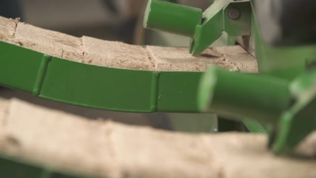 a close-up of pressed wooden briquettes coming out of the briquettes line. biomass fuel and environmental protection concept - биомасса возобновляемая энергия стоковые видео и кадры b-roll