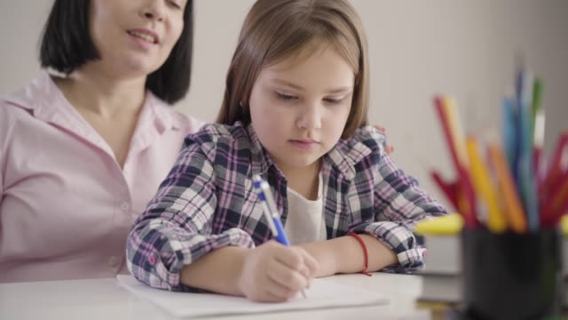 Close-up of pretty brunette Caucasian schoolgirl sitting with mom and writing in exercise book. Adult smiling mother helping daughter with homework. Support, education, studying.