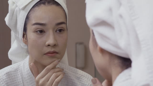 Close-up of pretty woman looking at mirror in bathroom looking for imperfections, facial wrinkles or acne on her skin.