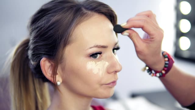 Closeup of professional makeup artist applying concealer to skin of young woman with brush to cover dark circles and make face look brighter. Slowmotion shot video