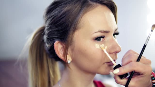 closeup of professional makeup artist applying concealer to skin of young woman with brush to cover dark circles and make face look brighter. slowmotion shot - tavolozza video stock e b–roll