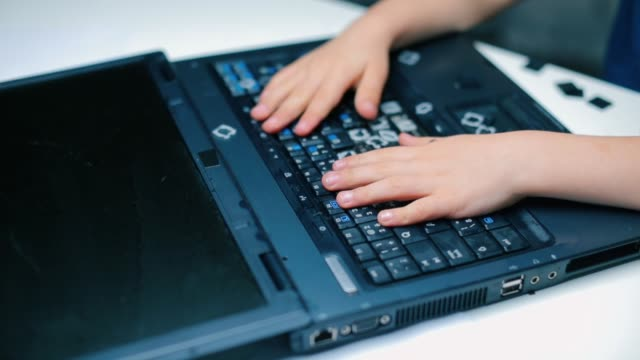 Close-up of pushing buttons on a broken laptop.