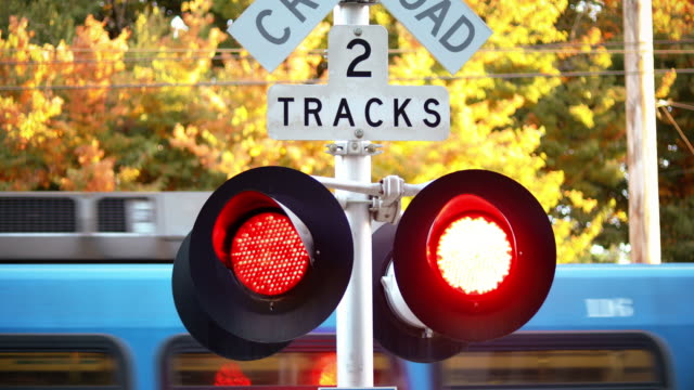 Close-up of railroad crossing sign with red lights flashing