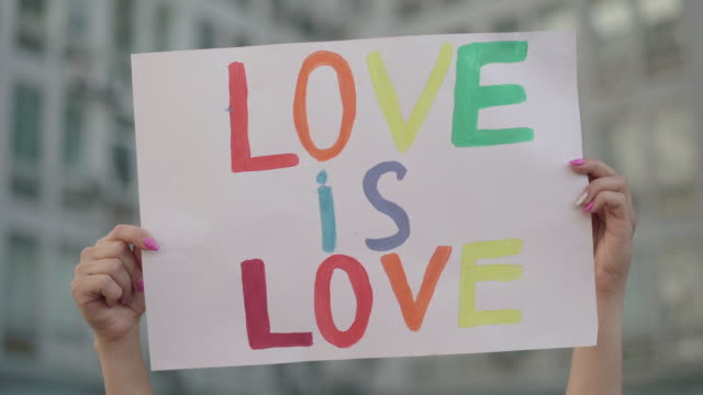 Close-up of raised Love is love banner in female Caucasian hands. Unrecognizable lesbian activist holding poster with slogan against homophobia. Young woman on gay pride parade. Close-up of raised Love is love banner in female Caucasian hands. Unrecognizable lesbian activist holding poster with slogan against homophobia. Young woman on gay pride parade. pride stock videos & royalty-free footage