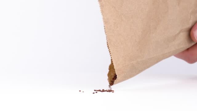 stockvideo's en b-roll-footage met close-up van rode quinoa zaden morsen uit eco papier pack. gluten vrije superfoods. geïsoleerd, op witte achtergrond - nerf