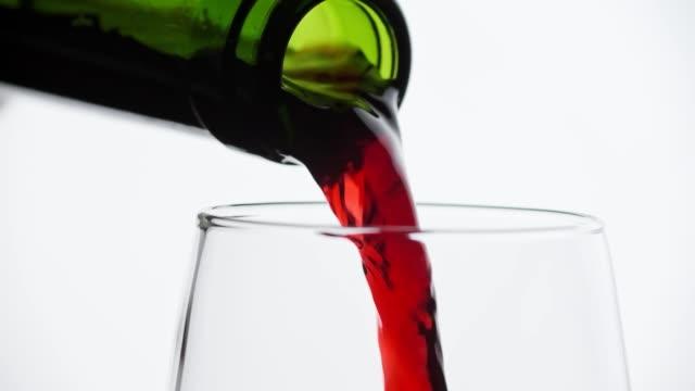 nahaufnahme von rotwein gießen in weinglas auf weißem hintergrund. makro-schuss - cabernet sauvignon traube stock-videos und b-roll-filmmaterial