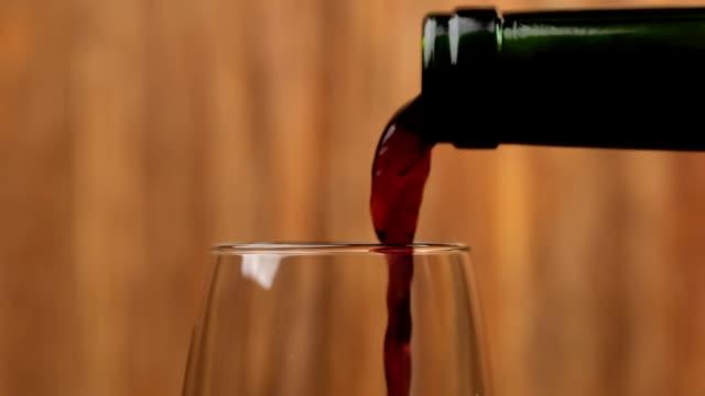 nahaufnahme von rotwein gießen in weinglas auf holzhintergrund. makro-schuss - cabernet sauvignon traube stock-videos und b-roll-filmmaterial