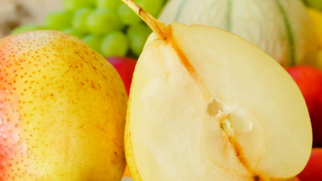 Closeup of ripe juicy pear Closeup of ripe juicy pear on a background of a still-life of fresh fruit pear stock videos & royalty-free footage
