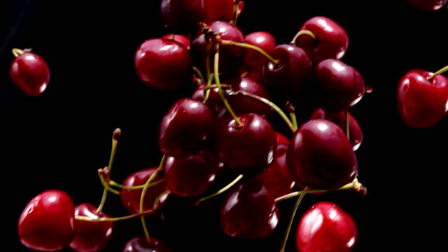 Close-up of ripe red cherry falling diagonally on a black background