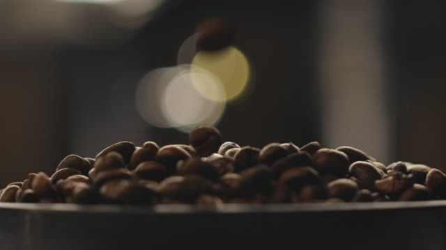 Close-up of roasted coffee beans falling