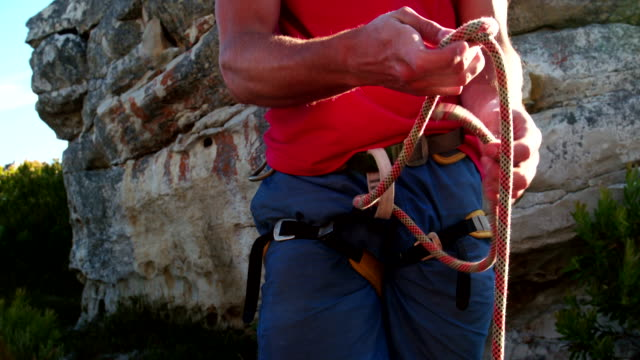 Closeup of rock climber hand's tying knot with belaying rope video