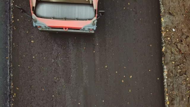 närbild av rullmaskin trycka ny asfalt. - wheel black background bildbanksvideor och videomaterial från bakom kulisserna