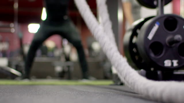 Close-up of rope for a gym, with which a man exercises in the gym Close-up of rope for a gym, with which a man exercises in the gym. Male athlete on floor beats sports equipment to develop endurance and strength. cross training stock videos & royalty-free footage
