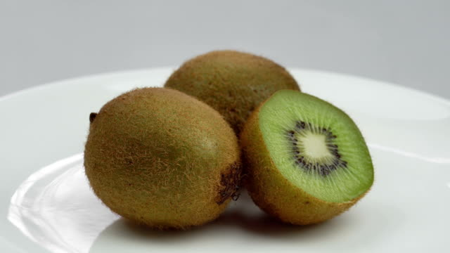 närbild av roterande kiwifrukt på vit bakgrund - kiwifrukt bildbanksvideor och videomaterial från bakom kulisserna
