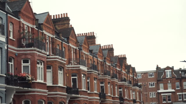 Close-up of Row of typical English terraced brick houses against the grey sky in autumn day. Action. Traditional English architecture video