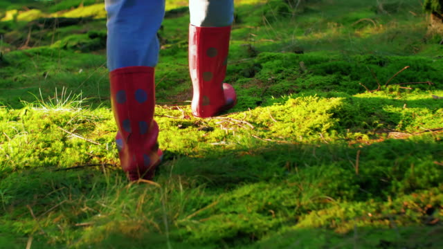 Close-up of rubber boots walking in a forest
