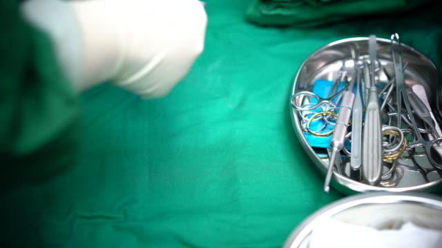 4k: scrub hemşire tıbbi aletleri, cerrahi ve acil kavramı alarak yakın çekim - cerrahi önlük stok videoları ve detay görüntü çekimi
