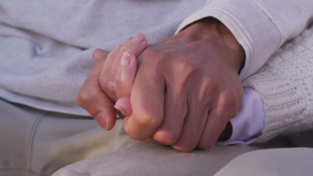 Closeup of senior couple holding hands video