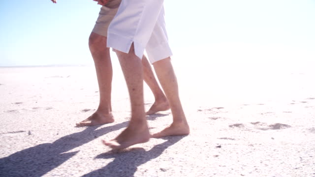 Close-up of senior couple's legs and feet walking in the sand video