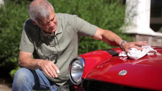 primo piano di uomo anziano lucidatura auto - lucidare video stock e b–roll