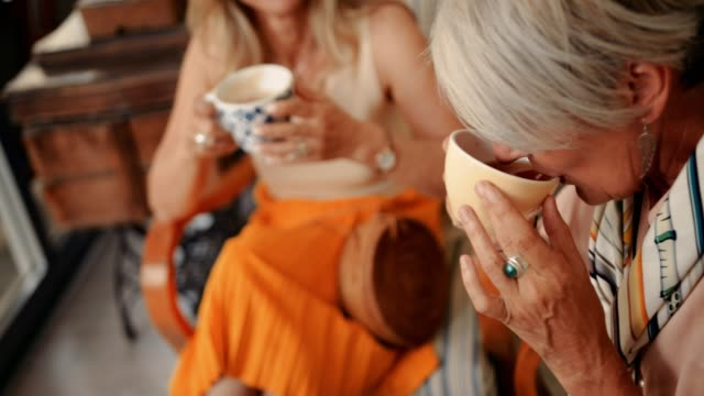 close-up of senior woman drinking tea with friends at cafe - attività del fine settimana video stock e b–roll