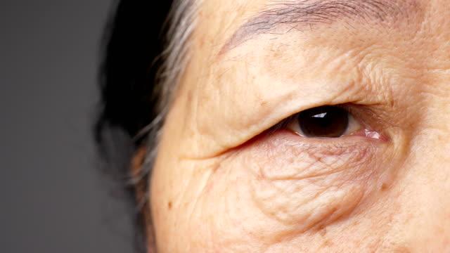 close-up of senior woman's eye - морщинистый стоковые видео и кадры b-roll