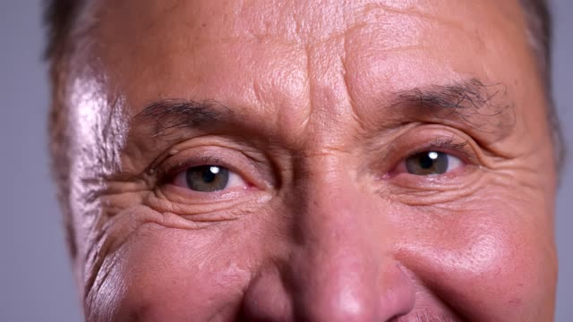 closeup of senior wrinkled caucasian male gray eyes looking straight at camera with happy facial expression - vicino video stock e b–roll
