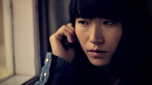 vídeos de stock, filmes e b-roll de close-up da menina asiática serena, sentado perto da janela. - 16 17 anos