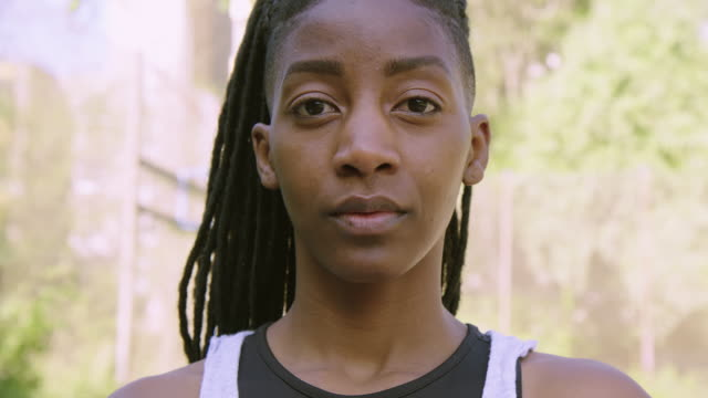 Close-up of serious female basketball player Panning shot of serious female basketball player. Close-up portrait of confident woman is at streetball court. She is having dreadlocks. black people stock videos & royalty-free footage