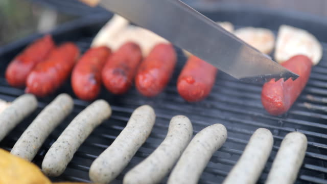 Close-up of serving tongs arranging sausages
