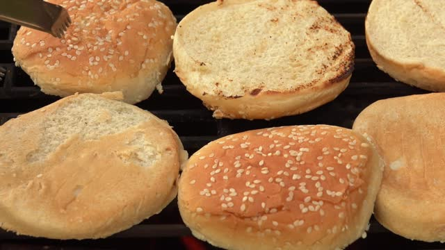 Close-up of sesame burger buns flipped on the grill grid Close-up of sesame burger buns flipped on the grill grid above the flames flames bun bread stock videos & royalty-free footage