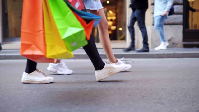 vídeos de stock e filmes b-roll de close-up of sexy slim women's legs walking along the street with colorful shopping bags - tote bag