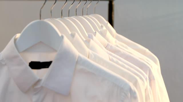 Close-up of shirts hanging on hanger 4k Close-up of shirts hanging on hanger against white wall 4K 4k coathanger stock videos & royalty-free footage