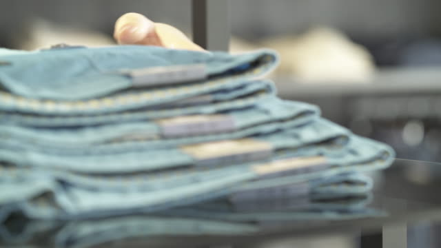 A close-up of shop assistant placing blue male trousers onto a shelf in a clothing shop. Fashion boutique routine work A close-up of shop assistant placing blue male trousers onto a shelf in a clothing shop. Fashion boutique routine work positioning stock videos & royalty-free footage