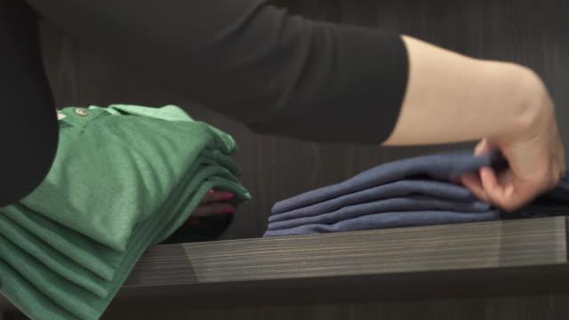 vídeos y material grabado en eventos de stock de un close-up de asistente de la tienda colocando coloridas camisetas elegantes en un estante en la tienda de ropa del hombre. trabajo de rutina boutique de moda - moda playera