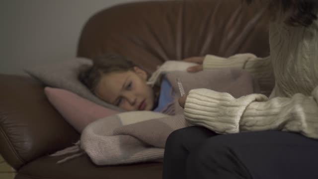 Close-up of sick little girl lying under blanket at home. Sad child has fever Close-up of sick little girl lying under blanket at home. Sad child has fever. Young caucasian mother checking daughter's temperature on thermometer. Focused on the foreground. shivering stock videos & royalty-free footage